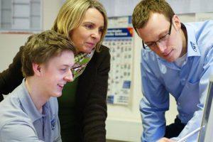 Drei Mitarbeiter von NFT beraten über einen PC-Monitor gebeugt über ein Projekt