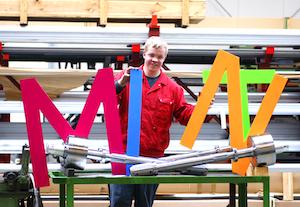 Industriemechaniker Christoph mit MINT-Buchstaben vor Wickelwalzen