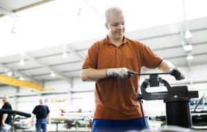Industriemechaniker Christoph Hoffmann bearbeitet lächelnd mit der Feile ein Metallteil an der Werkbank