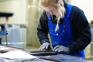 Azubi Melanie Klare reisst Metall an der Werkbank an