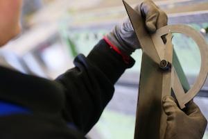 Konstruktionsmechanikerin misst den Winkel eines Bauteiles aus Metall