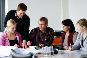 Produktdesigner Eugen in Besprechung mit drei weiteren Kolleginnen und Kollegen
