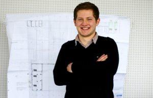 Der Technische Produktionsdesigner Eugen Braun steht lachend vor einer weißen Wand, an der eine technische Zeichnung befestigt ist