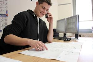 Systemplaner Marco bespricht am Telefon eine vor sich liegende technische Zeichnung