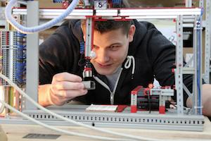 Systemplaner Azubi Marco arbeitet an Modell-Automatisierungsanlage