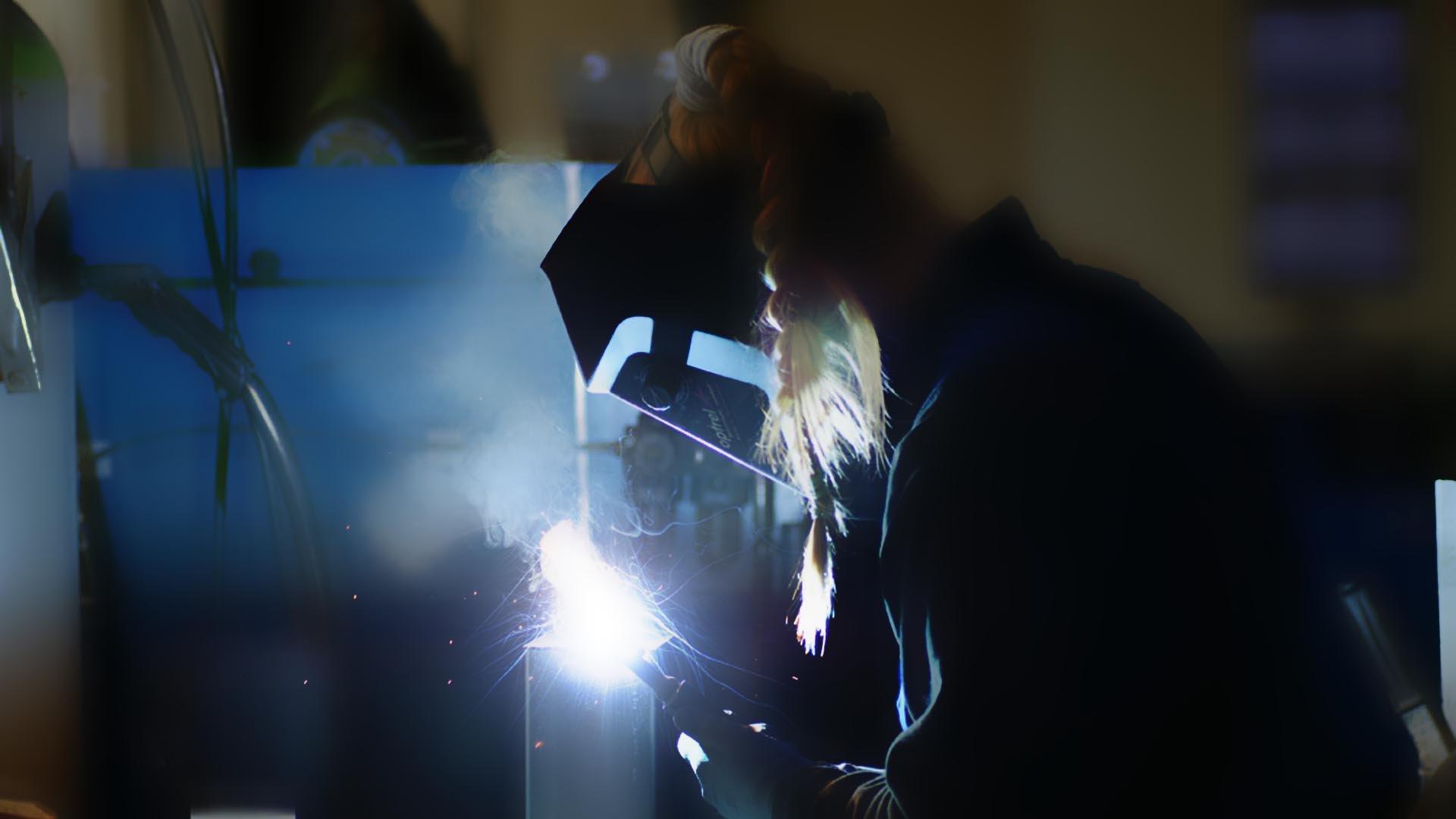 MINT Headerfoto: Junge Frau mit Helm und Zopf bei Schweißarbeiten
