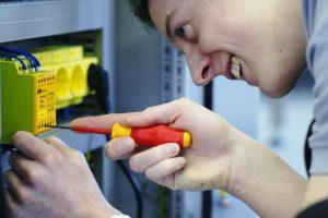 Azubi Elektroniker Automatisierungstechnik arbeitet mit Schraubendreher am Schaltschrank
