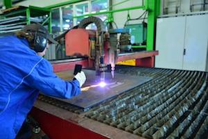 Mann schneidet Metall an morderner Bearbeitungsmaschine