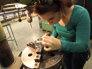 Schülerin bearbeitet in einer Werkshalle eine Metallteil an einer Standbohrmaschine