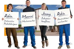 4 Azubis stehen nebeneinander und tragen Schilder mit ihren Namen sowie ihrem Ausbildungsberuf