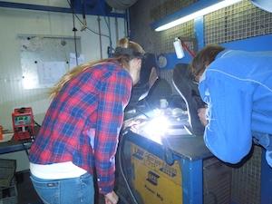 Mädchen bei einem Miss MINT-Club beim Schweissen angleitet von einem Mechaniker