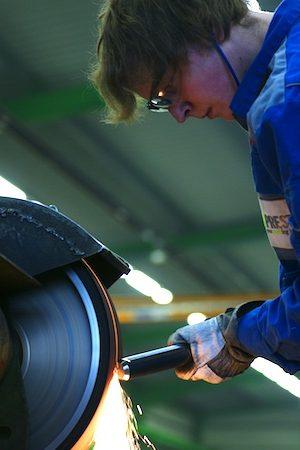 Konstruktionsmechaniker entgratet Metallteil