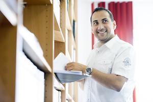 Spanntec Mitarbeiter steht lächelns mit Akten vor einer Regalwand