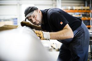 Mitarbeiter kontrolliert eine Wickelwalze aus Metall
