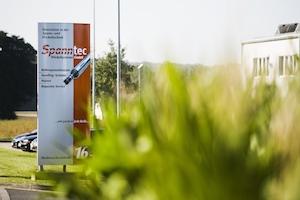 Aussenaufnahme des Unternehmens Spanntec mit großem Firmenschild im Vordergrund ist ein grüner Busch