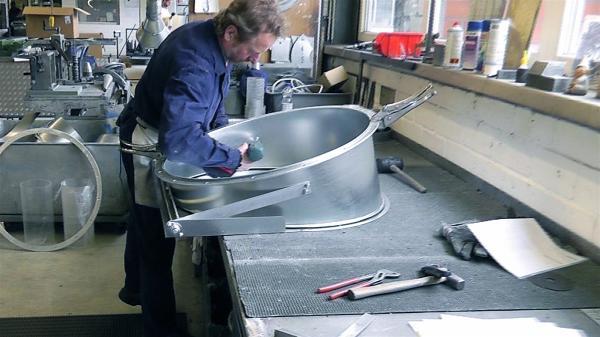 Mitarbeiter bearbeitet ein Bauteil für eine Filteranlage aus Feinblech mit einem Hammer