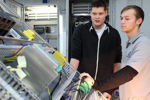 Zwei Mitarbeiter von NFT stehen vor einem Schaltschrank