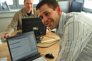 Mann am Laptop dreht sich um und lacht in die Kamera