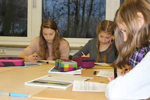 4 Mädchen beugen sich bei den Profilings über ihre Fragebögen und füllen diese konzentriert aus