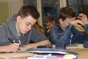 Zwei Jungen sitzen bei den Profilings im Klassenzimmer am Pult über ihre Fragebögen gebeugt