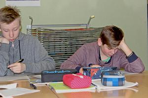 Zwei Schüler sitzen am Pult und füllen konzentriert Fragebögen für ihre Profilings aus