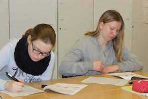 Zwei Mädchen sitzen am Pult und füllen konzentriert Fragebögen für ihre Profilings aus