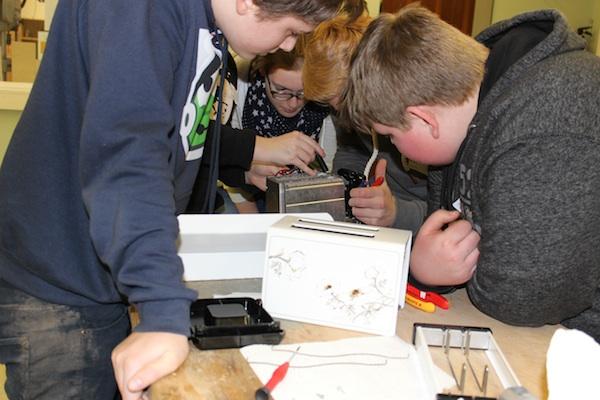 Eine Gruppe von Schülern der 2. Reparierwerkstatt steht eng gedrängt und dicht gebeugt über einem Toaster und überlegt, was die Ursache des Defekts sein könnte