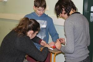Bei der Eröffnung der 2. Reparierwerkstatt knien zwei Jungs an einem Stuhl und versuchen ein Elektrogerät zu reparieren, dabei werden sie von einer studentischen Betreuerin unterstützt