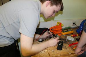 Elektronik-Azubis überprüft in der 2. Reparierwerkstatt mit einem Phasenprüfgerät die elektrische Spannung in einem defekten Teil