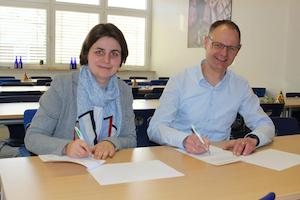 Schulleiterin Christiane Althoff und NFT-Geschäftsführer Frank Haacks sehen lachen in die Kamera während sie die Kooperationsverträge für die 2. Reparierwerkstatt von Let's MINT unterzeichnen