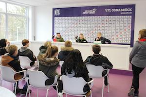 Schüler spielen im Presseraum des VFL Osnabrück eine Pressekonferenz nach, 3 Jungen sitzen hinter Mikrofonen, die anderen Schüler hören zu