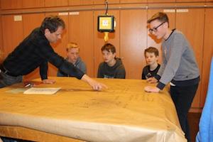 Lehrer und Schüler besprechen an einem Tisch die Ergebnisse des World Café beim 1. Werkstatttreffen