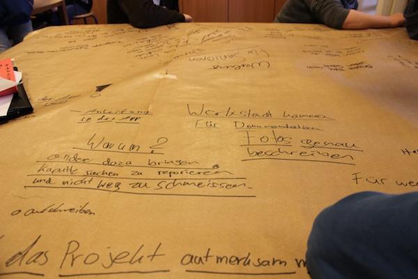 Ergebnisse des 1. Werkstatttreffens, das Foto zeigt handschritliche Notizen der Schüler auf der Papiertischdecketischdecke eines Tisches geschrieben