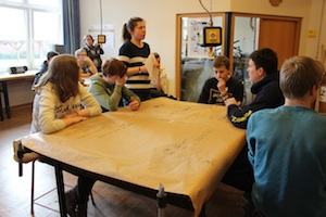 Schüler beim 1. Werkstatttreffen sitzen um einen Tisch an dem eine Betreuerin steht, alle hören zu