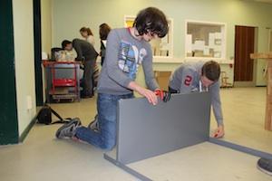 Zwei Jungen der Ibbenbürener Tüftler-AG knien auf dem Boden und schrauben eine Werkbank zusammen