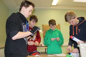 Vier Jungen der Ibbenbürener Tüftler-AG stehen im Halbkreis um eine Werkbank und nehmen Teile der Werkstatteinrichtung in die Inventarlisten auf