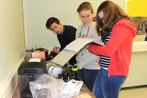 Zwei Schülerinnen und ein Schüler der Ibbenbürener Tüftler-AG stehen an einer Werkbank und nehmen defekte Geräte in die Reparaturlisten auf