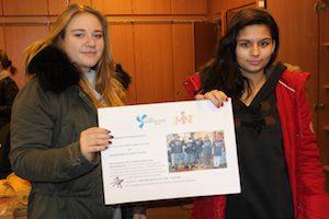 Zwei Schülerinnen halten Plakat mit Informationen über die Reparierwerkstatt in die Kamera