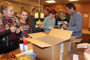 Schüler packen Kartons in Werkstatt aus