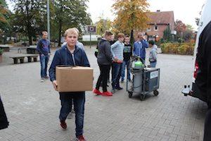 Junge trägt Pappkarton mit Werkstatteinrichtung über den Schulhof