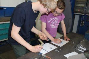 Zwei Schüler beugen sich über technische Zeichnungen und besprechen die Aufgabe
