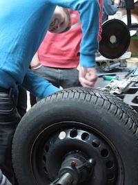 Reparatur 4.0: Ein Schüler wuchtet einen Reifen aus