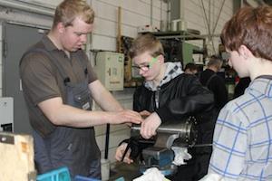 Reparatur 4.0: Zwei Schüler montieren unter Anleitung eines Industriemechanikers eine Wickelwalze