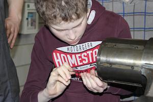 Reparatur 4.0: ein Schüler befestigt mit Schraubendreher eine Komponente innerhalb einer Wickelwalze