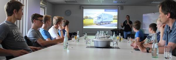 Schueler sitzen am Konferenztisch und hoeren sich einen Vortrag ueber die Arbeit der AWIGO an