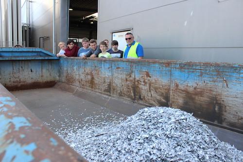 Exkursion Elektrorecycling: Schüler blicken über den Rand eines Containers, in den Schnipel rieseln