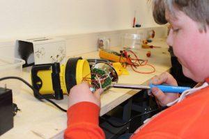 Reparaturen durch Schüler: Junge lötet Drähte an einem aufgeschraubten Akku-Halogen-Strahler