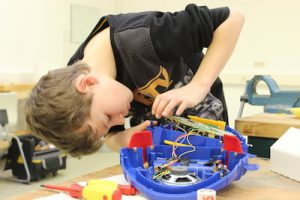 Reparaturen durch Schüler: Junge beugt sich über einen aufgeschraubten Kinder-CD-Spieler aus buntem Kunststoff