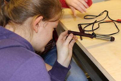 Reparaturen durch Schüler: Mädchen begutachtet eine aufgeschraubte Elektrohaarbürste