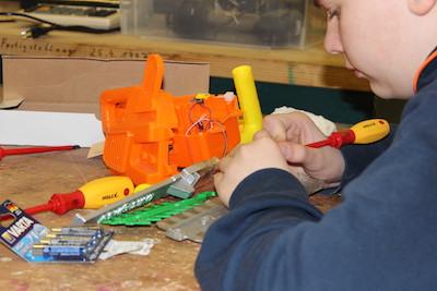 Reparaturen in der Schülerwerkstatt: Großaufnahme von Junge mit Schraubendreher an einem auseinander gebauten Kunststoff-Spielzeug